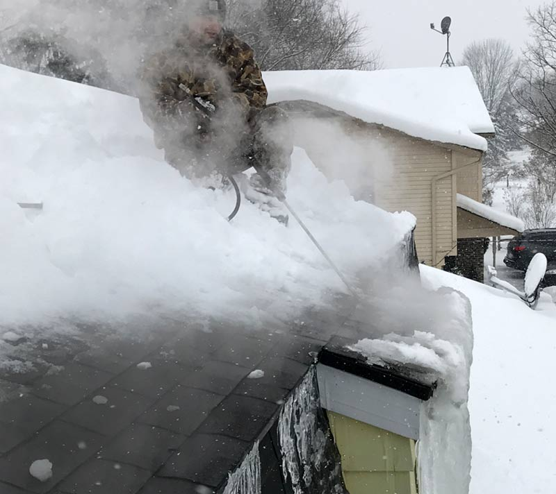 roof cleaner in grand rapids michigan removing ice dam with steam on roof
