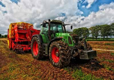 pressure washing farm equipment on muddy tractor in field