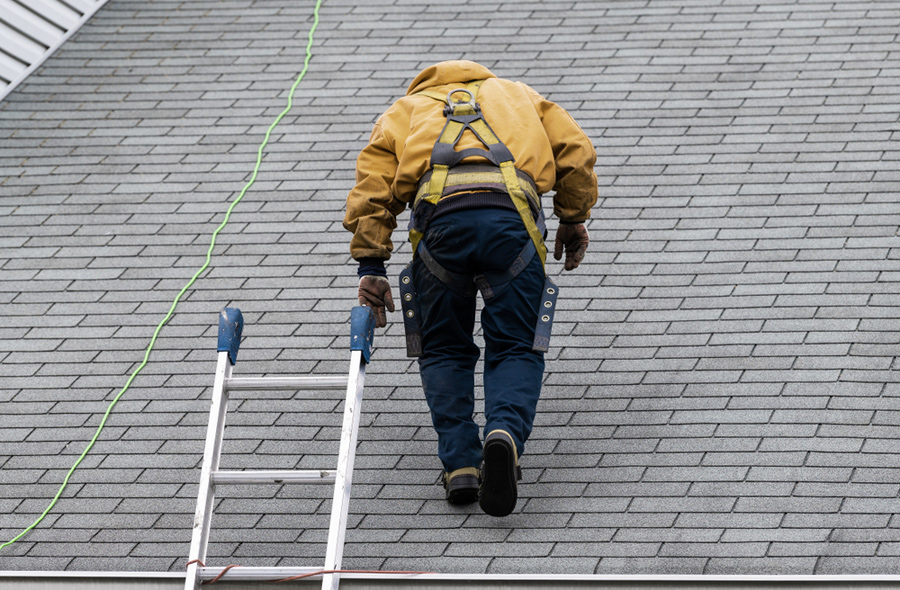 man performing roof inspection near grand rapids, michigan